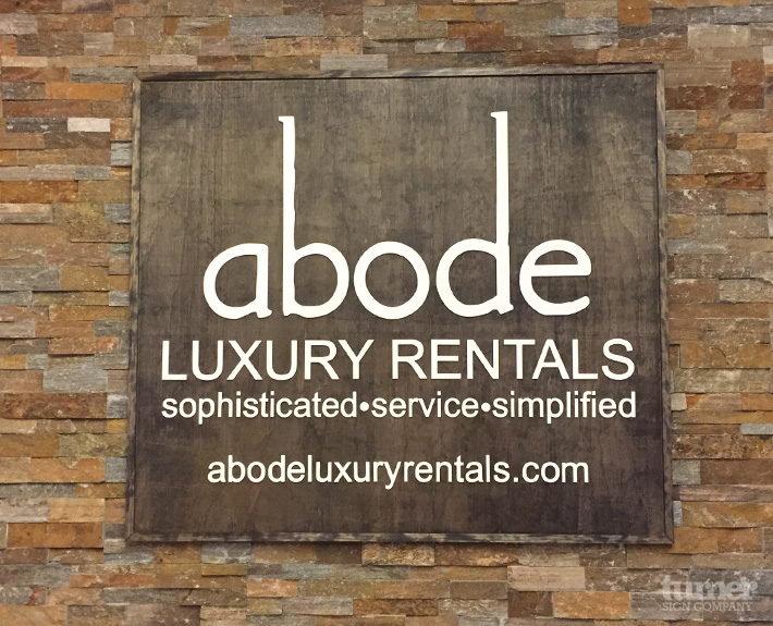 Abode Lobby Sign with 3d letters on dark wood background
